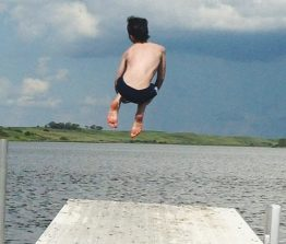 Boy jumping into the lake off a dock